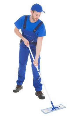 Full length of male servant mopping floor over white background