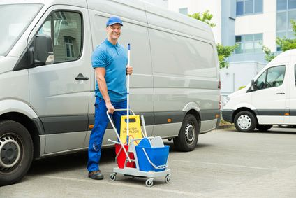 Happy Male Cleaner In Front Of Van With Cleaning Equipments