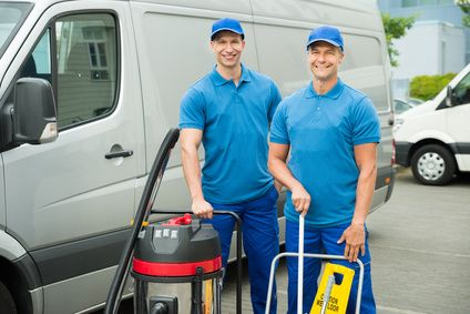 Two Happy Male Cleaners Standing With Cleaning Equipments In Front Van