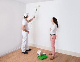 Young Housewife Looking At Painter Painting Wall In House